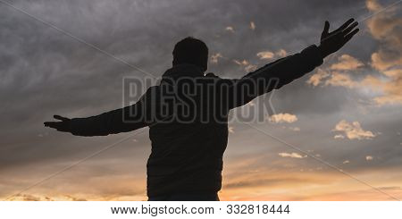 View From Behind Of A Man Standing With His Arms Wide Open Under A Glorious Cloudy Evening Sky.