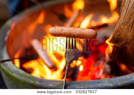 A Photo Of Sausage Sizzling On Open Fire During Camping.