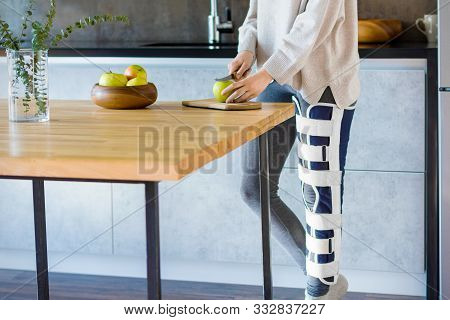 Girl With Broken Leg Is Standing In Kitchen And Cooking. Injured Woman Wearing Supporting Compressio