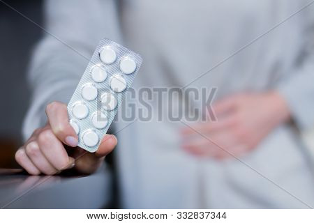 Woman In Grey Clothes Is Holding Hands On Belly. Girl Is Feeling Bad And Going To Take Pills. Sudden