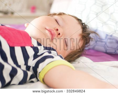 Childrens Daytime Sleep. Funny Baby Sleeping On The Back Of The Bed At Home. Childrens Day Position.