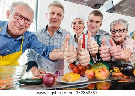 Trainees and their nutritionist chef in a training kitchen showing thumbs