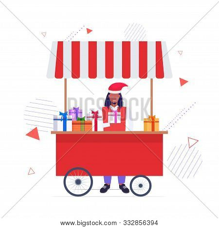 African American Man In Santa Hat Selling Present Boxes Christmas Market Fair Concept Stall With Wra