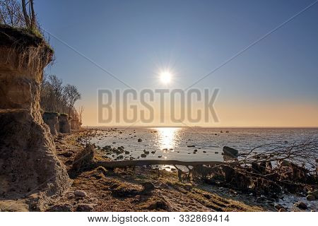Evening Sun With Rays Reflected In The Water At The Steep Coast Cliff Of The German Island Poel In T