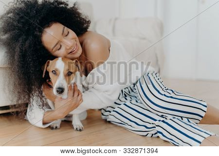 Affectionate Young Woman Hugs Dog With Love And Care, Keeps Eyes Closed From Pleasure, Smiles Gently