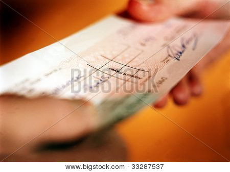 Person handing over check in financial transaction.
