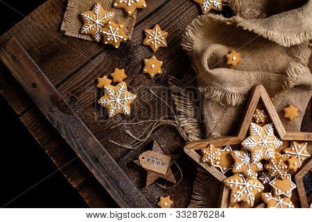 Overhead Shot Of Christmas Snowflakes Shaped Orange Cookies With Beautiful Icing Decoration In Woode