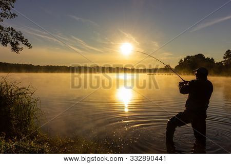 Angler Silhouette In The Lake During Hazy Summer Sunrise