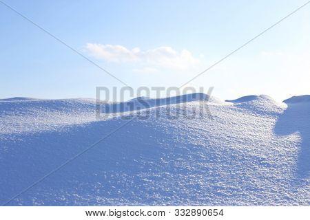 Winter  landscape. A large beautiful snowdrift and blue sky.  A big snow drift