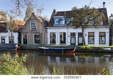 Nostalgia quayside with old boats and historical houses in Schipluiden in the Netherlands poster
