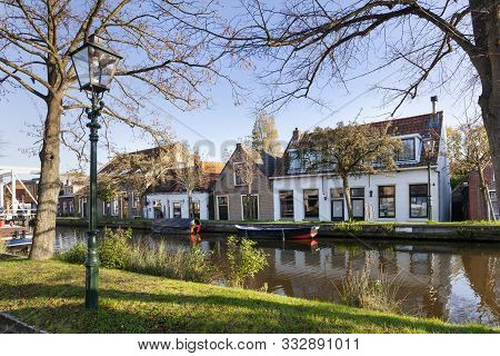 Nostalgia quayside view with old boats and historical houses in Schipluiden in the Netherlands poster