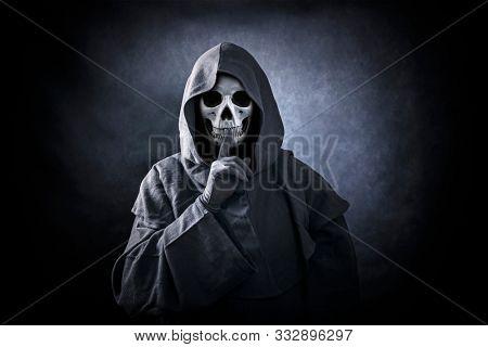 Grim reaper showing hush sign