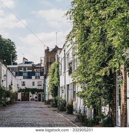 Row of typical mews houses in London, UK, street view, selective focus. Real estate and property concept. poster