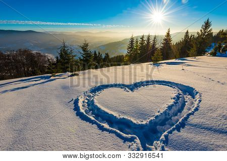 Heart Trampled On The Snow With Feet In A Snowdrift On A Hillside With A Gorgeous View Of The Conife