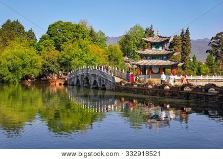 Lijiang, China - April 27, 2019: Tourists Over The Suocui Bridge With Moon Embracing Pavilion On The