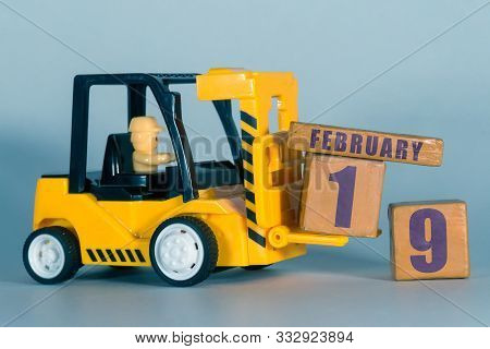 February 19th. Day 19 Of Month, Construction Or Warehouse Calendar. Yellow Toy Forklift Load Wood Cu