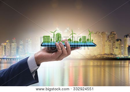 Hand holding tablet with mini ecosystem and clean energy