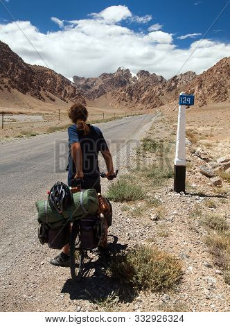 Pamir Highway Or Pamirskij Trakt With Biker And Pamir Mountains In Tajikistan. Landscape Around Pami
