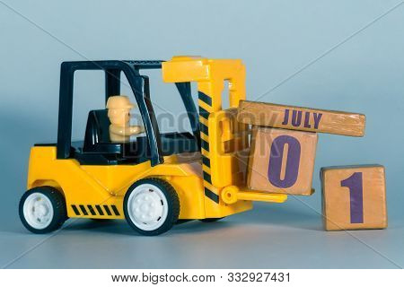 July 1st. Day 1 Of Month, Construction Or Warehouse Calendar. Yellow Toy Forklift Load Wood Cubes Wi