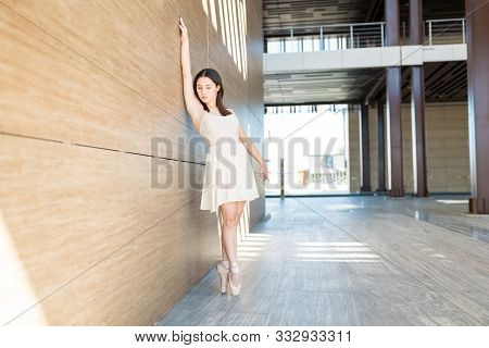 Young Ballerina Standing On Tiptoe With Hand Raised By Wall During Dance Performance On Street