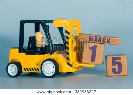 March 15th. Day 15 Of Month, Construction Or Warehouse Calendar. Yellow Toy Forklift Load Wood Cubes