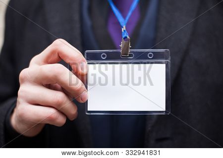An Empty Plastic Identification Card In The Hand Of A Man On The Background Of A Jacket And A Blue S