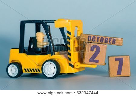 October 27th. Day 27 Of Month, Construction Or Warehouse Calendar. Yellow Toy Forklift Load Wood Cub