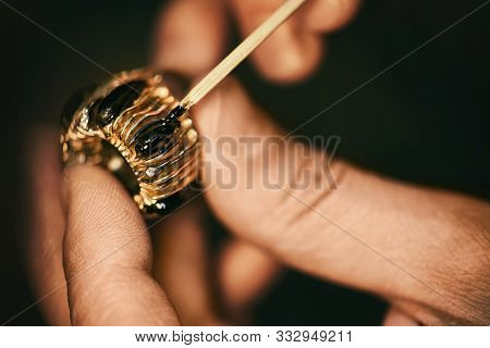 A Jeweler Is Gluing The Preciousgem To The Gold Ring.