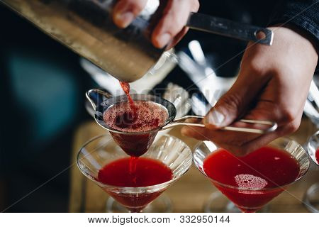Close-up Of Expert Bartender Making Red Cocktail On The Bar
