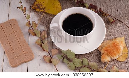 A Hot Cup Of Coffee With A Bar Of Chocolate On The Table In A Cafe. Composition Of A Delicious Coffe