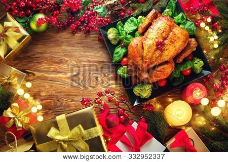 Christmas Dinner. Roasted chicken. Winter Holiday table served, decorated with candles and xmas baubles. Roast turkey over wooden background with Christmas tree, table setting family dinner with gifts