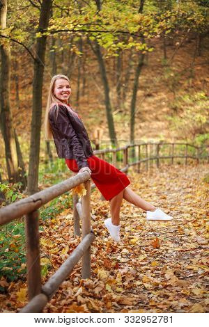 Happy Young Woman In A Red Dress Carelessly Having Fun In A Forest Park Enjoying Nature