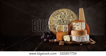 Variety Of Cheeses On A Wooden Board With Nuts And Honey