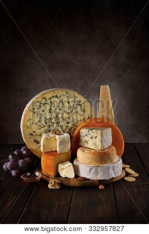 Many Sorts Of Cheeses On A Wooden Board With Nuts And Honey