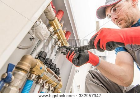 Residential House Floor Heating Valves Adjustment. Plumbing And Heating Technician At Work.