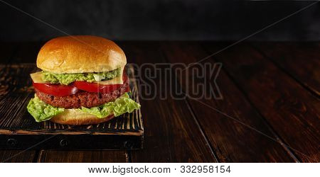 Homemade Vegetarian Burger On Wooden Board On Dark Background