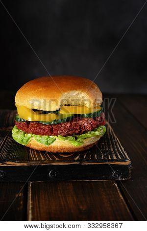 Bitten Vegetarian Burger On Wooden Board On Dark Background