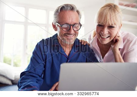 Mature Couple At Home Looking Up Information About Medication Online Using Laptop