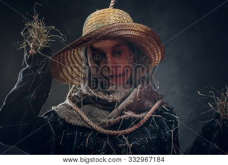 Creative Girl In Straw Hat And Spooky Makeup Is Posing For Photographer With Rope On Neck.