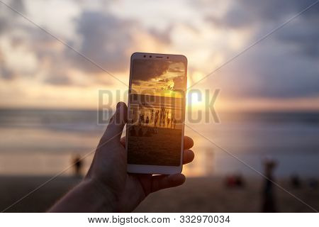 Using A Samrtphone. Photographing Sunset On A Mobile Phone.