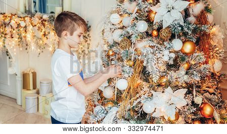 Young Boy Decorating Christmas Tree On Christmas Eve At Home. Young Kid In Light Bedroom With Winter
