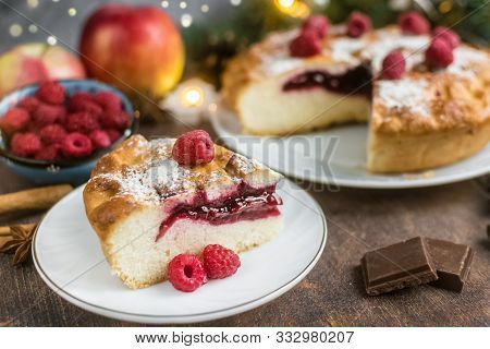 Delicious Christmas Raspberry Pie With Berry Filling And Icing Sugar And Spices On A Dark Background