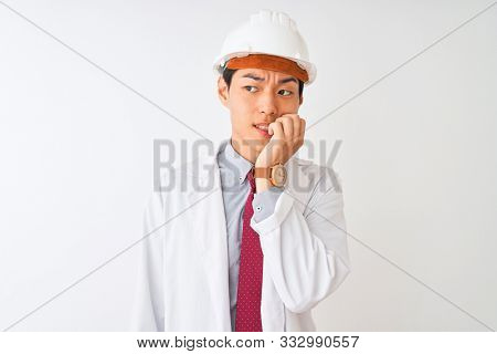 Chinese architect man wearing coat and helmet standing over isolated white background looking stressed and nervous with hands on mouth biting nails. Anxiety problem.