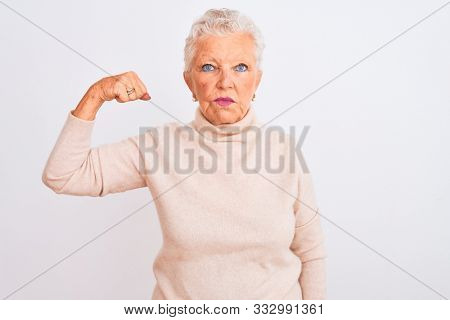 Senior grey-haired woman wearing turtleneck sweater standing over isolated white background Strong person showing arm muscle, confident and proud of power