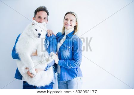Young beautiful couple holding dog standing over isolated white background