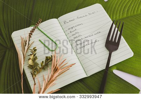 Plant-based Diet Conceptual Still-life, Notebook With Food Category List On Tropical Leaf With Fork