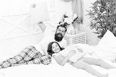 Happy fatherhood. Man bearded hipster with childish hairstyle colorful ponytails and daughter in pajamas. Guy and girl relaxing in bedroom. Pajamas style. Having fun pajamas party. Slumber party. poster