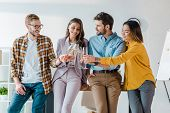 cheerful businessmen and multicultural businesswomen toasting champagne glasses in office poster
