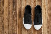 Black gumshoes with a white sole stand on a wooden floor. Top view of classic sneakers, wooden background, copy space. poster