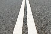 Two white lines on an asphalt road poster